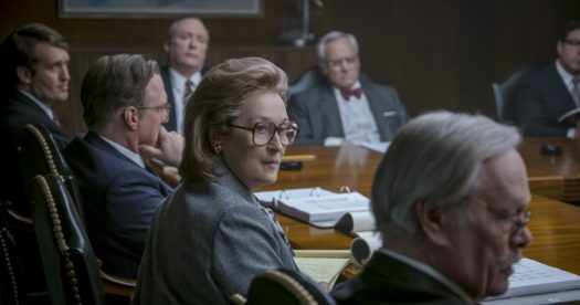 Foto da cena em que a atriz Meryl Streep está sentada à mesa com vários homens.