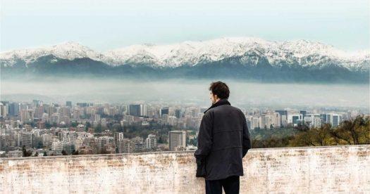 """Cena do documentário """"Santiago, Itália"""", de Nanni Moretti: homem olha de um lugar alto para uma paisagem da cidade de Santiago"""