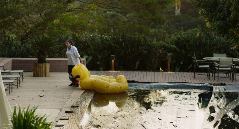 Cena do filme Três Verões, de Sandra Kogut: Regina Casé à beira de uma piscina puxando uma bóia em forma de pato amarelo